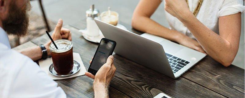 Experiencia de usuario - Dos personas con smartphone y ordenador